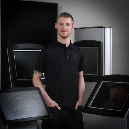 Kenneth Madsen standing in front of kiosks