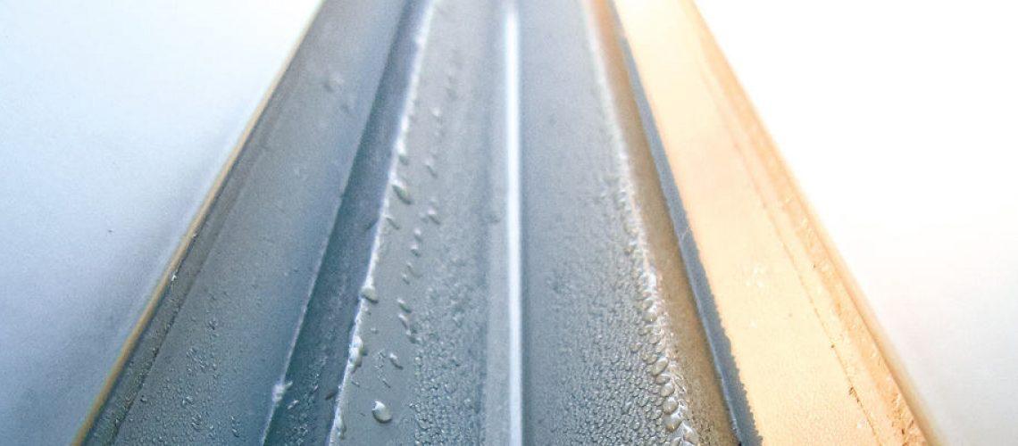 Side of anodized aluminium still wet from acidic bath